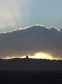 a photo of a chruch tower in the sunset, with rays of light