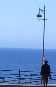a photo of the sea at the end of a street, with an outline of a person.