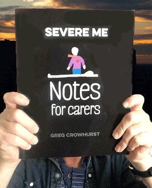a picture of Greg holding Severe ME, Notes for Carers up