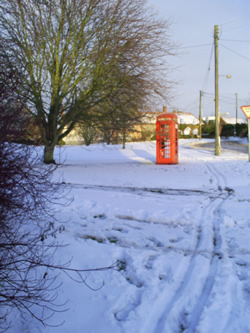 a photo of a red telephone box in the snow